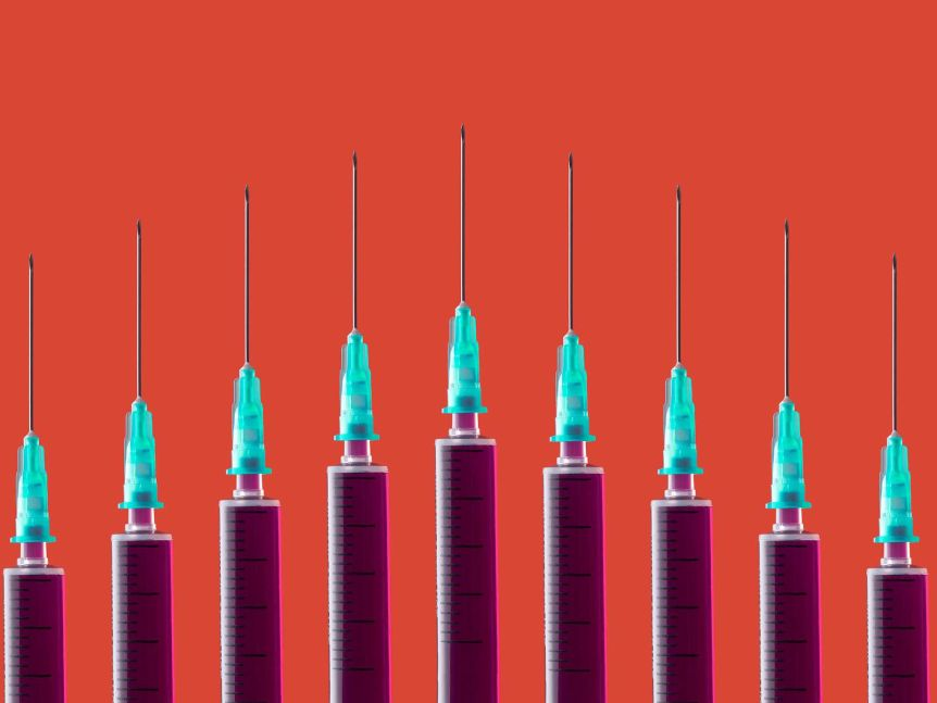 Multiple syringes organized in a pattern over orange background.