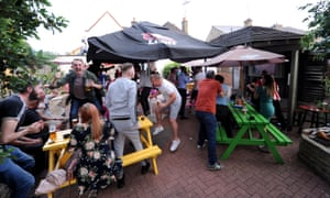 Brentford fans celebrate their team's first goal as they watch the match in the beer garden at The New Inn, one of the pubs located by each corner of Griffin Park.