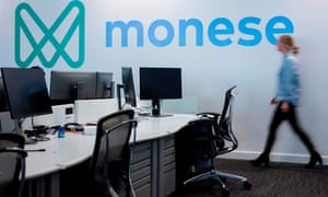 An employee of mobile phone app-based 'neo-bank', Monese walks past the company's logo at its offices in London