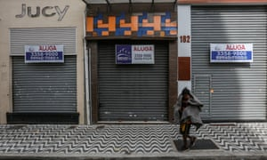 A homeless man walks in front of a shuttered shop with a 'For Lease' sign in downtown amidst the coronavirus pandemic on 29 June 2020 in Sao Paulo, Brazil.