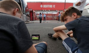 Fans who aren't allowed into Griffin Park because of Coronavirus restrictions, have to make do watching the action on a tablet outside the stadium.