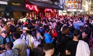 Revellers drink and socialise in the street during the evening in Soho