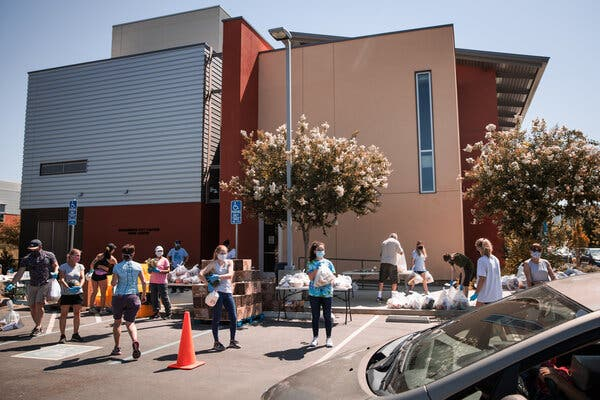 """Volunteers at a food bank in Davis, Calif., last week. """"The path forward for the economy is extraordinarily uncertain,"""" the Federal Reserve chair said Wednesday."""