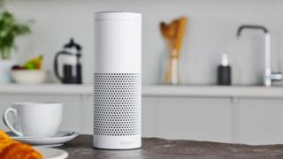 A white Amazon Echo smart speaker stands on a kitchen countertop with staged coffee and croissant