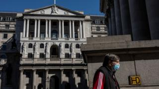 A man wearing a mask walks past the Bank of England in London