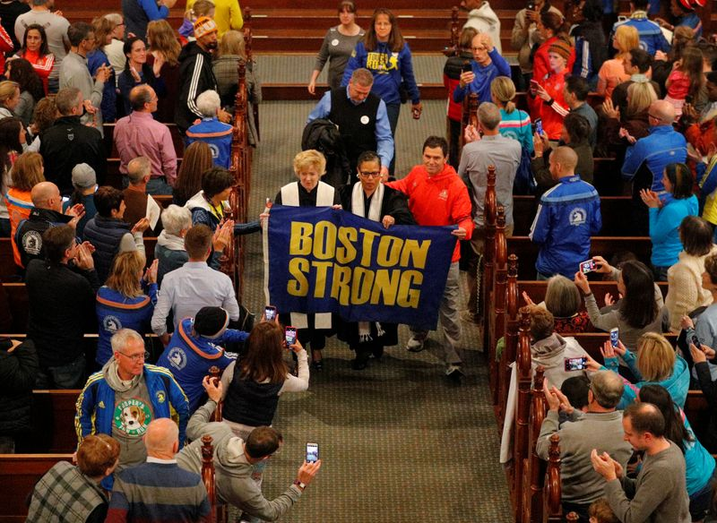 © Reuters. Boston Marathon bombing witness Carlos Arredondo blesses the runners during a service at Old South Church in Boston
