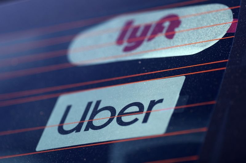 © Reuters. FILE PHOTO:  Uber and Lyft signs are seen on a car in Redondo Beach