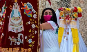 A woman wearing a protective mask takes part in the ceremony of delivery of a dress for the Virgin of the Assumption during the Catholic celebration of San Sebastian Mestizos Guild in Merida, Yucatan State, Mexico, on 9 August 2020 amid the coronavirus pandemic.