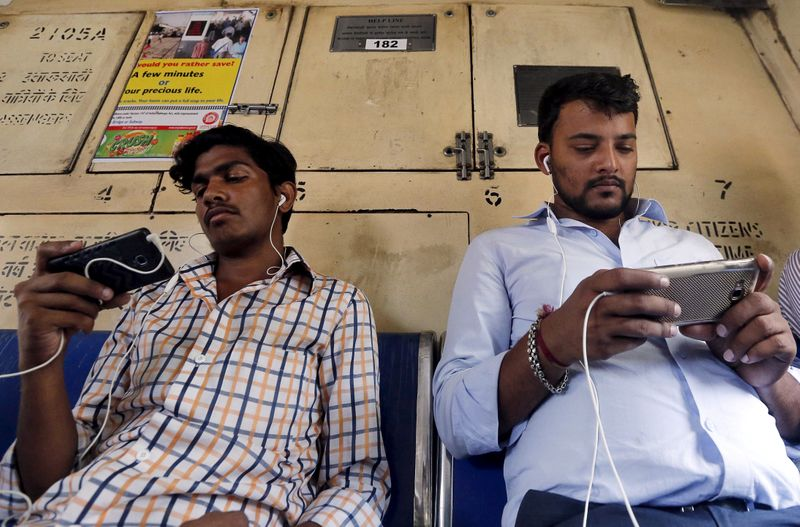 © Reuters. FILE PHOTO: Commuters watch videos on their mobile phones as they travel in a suburban train in Mumbai