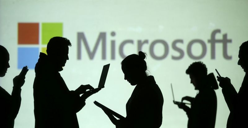 © Reuters. Silhouettes of laptop and mobile device users are seen next to a screen projection of Microsoft logo in this picture illustration
