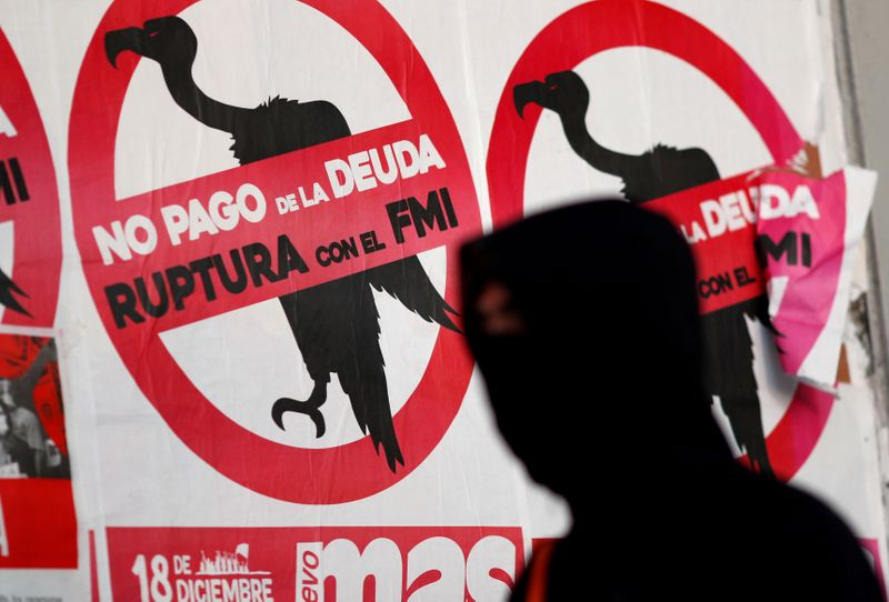 © Reuters. FILE PHOTO: A pedestrian wearing a face mask walks past posters on the street that read