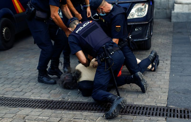 © Reuters. A person is detained by police officers during a protest against Spain's monarchy for the first time since former Spanish King Juan Carlos left the country amid an investigation into his involvement in a high-speed rail contract in Saudi Arabia, in M