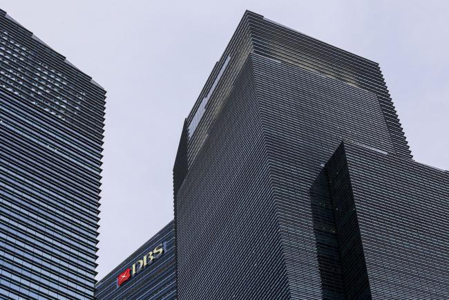 © Bloomberg. The DBS Group Holdings Ltd. logo is displayed atop Tower 3 of the Marina Bay Financial Centre in Singapore, on Wednesday, Feb. 12, 2020. The coronavirus outbreak rocked Singapore's financial district after an infection at the country's biggest bank prompted it to evacuate 300 workers.