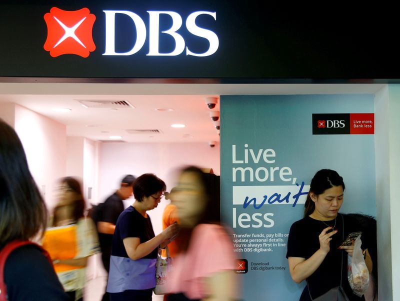 © Reuters. FILE PHOTO: FILE PHOTO: People walk past a DBS branch in Singapore