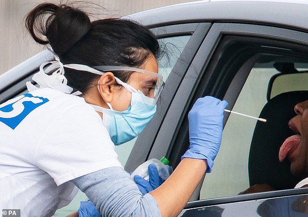 A medical worker takes a swab at a drive-in coronavirus testing facility at the Chessington World of Adventures Resort in south west London
