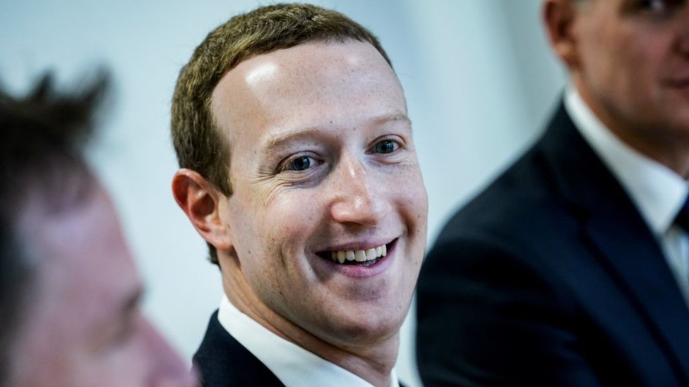 Facebook founder Mark Zuckerberg smiles at the camera in this close-up shot of a group, with other members obscured by the framing