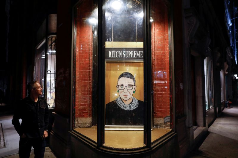 © Reuters. A person looks towards a painting in a storefront on Broadway of Associate Justice of the Supreme Court of the United States Ruth Bader Ginsburg who passed away in Manhattan, New York City