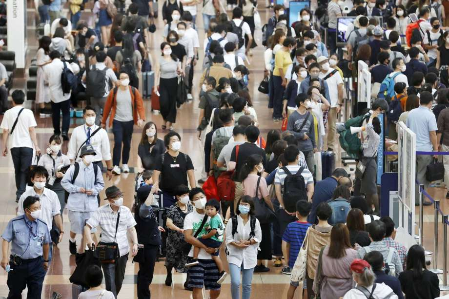 Travelers wearing face masks crowd at Haneda airport in Tokyo Saturday, Sept. 19, 2020, on the first day of the 4-day holiday. (Kyodo News via AP) Photo: 西沢幸恵, AP / Kyodo News