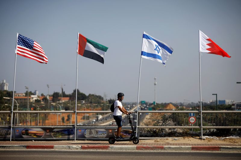 © Reuters. A man rides a scooter near the flags of the U.S., United Arab Emirates, Israel and Bahrain as they flutter along a road in Netanya