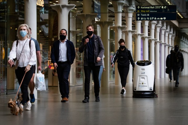 An Eco Bot 50 robot cleans and disinfects surfaces simultaneously with an automated scrubber dryer at St Pancras International, London (Credits: PA)