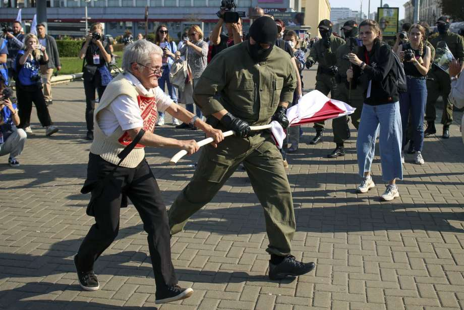 A police officer tries to take away an old Belarusian national flag from Nina Bahinskaya's hands during an opposition rally to protest the official presidential election results in Minsk, Belarus, Saturday, Sept. 26, 2020. Hundreds of thousands of Belarusians have been protesting daily since the Aug. 9 presidential election. Photo: TUT.by, AP / TUT.by