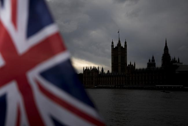 © Bloomberg. A British Union flag, also k{{0|now}}n as a Union Jack, flies from a tourist souvenir stall on the bank of the River Thames in view of the Houses of Parliament in London, U.K., on Monday, Oct. 28, 2019. The European Union looks set to grant the U.K. a delay to Brexit until Jan. 31, prolonging the uncertainty for businesses and citizens but removing the risk of a damaging no-deal split on Thursday. Photographer: Jason Alden/Bloomberg