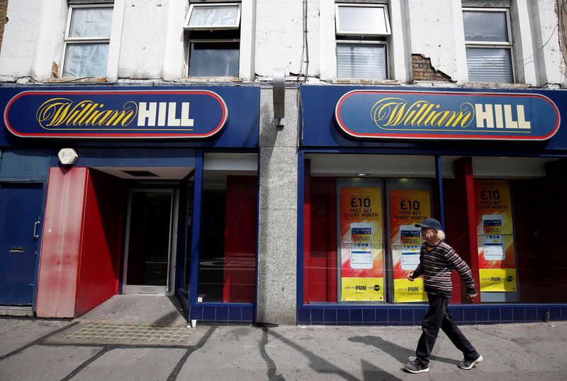 © Reuters. FILE PHOTO: A pedestrian walks past a William Hill betting shop in London