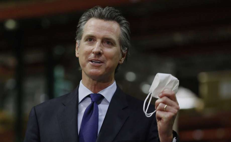 "FILE - In this June 26, 2020 file photo, Gov. Gavin Newsom holds a face mask as he urges people to wear them to fight the spread of the coronavirus during a news conference in Rancho Cordova, Calif. On Saturday, Sept. 26, 2020, Newsom signed a law that requires the state to house transgender prisoners based on their gender identity. The law does have an exception for ""management or security concerns."" Photo: Rich Pedroncelli, AP / Copyright 2020 The Associated Press. All rights reserved"