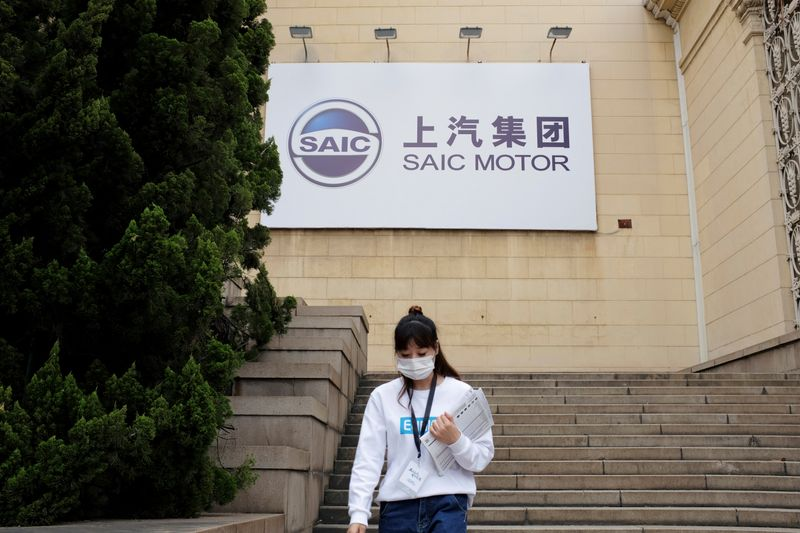 © Reuters. Woman wearing a face mask following the coronavirus disease (COVID-19) outbreak walks by a SAIC Motor logo at a sales event in Shanghai