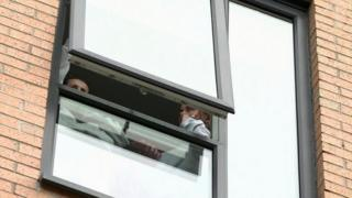 Two students look out the window of their accommodation at Manchester Metropolitan University