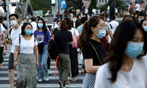 People wearing face masks walk across a street at a shopping area in Beijing, China 25 August 2020.