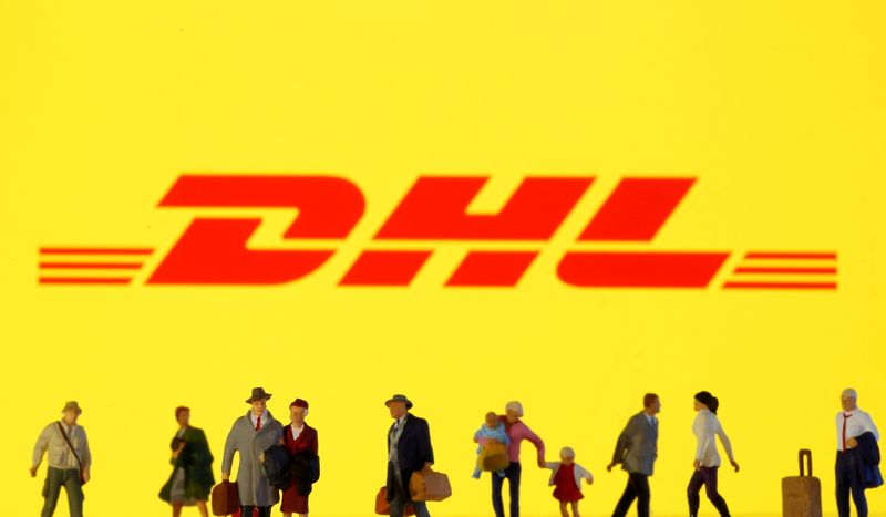 © Reuters. FILE PHOTO: Small toy figures are seen in front of diplayed DHL  logo