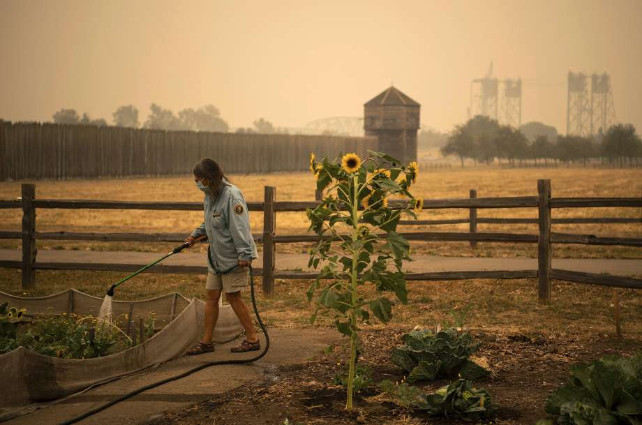 "Volunteer Elizabeth Stoltz of Heisson waters the Fort Vancouver Garden in Vancouver, Wash., Friday, Sept. 11, 2020. Stolz said things were extra dried out because of the wind and smoke. ""The wind sucks the life out of everything,"" she said. Stoltz said she is still not under evacuation from the Big Hollow Fire but her family made a plan in case it gets to that point. Clark County entered hazardous air-quality territory late Thursday as wildfire smoke traveling from other areas enveloped Southwest Washington. (Alisha Jucevic/The Columbian via AP) Photo: Alisha Jucevic, AP / @ The Columbian"