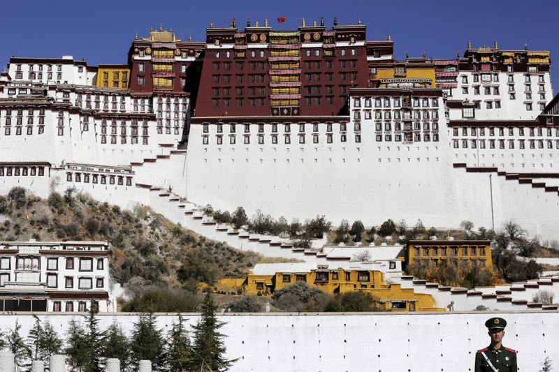 © Reuters. FILE PHOTO: A paramilitary policeman stands guard in front of the Potala Palace in Lhasa, Tibet Autonomous Region