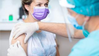 Nurse in protective gear giving patient a vaccination