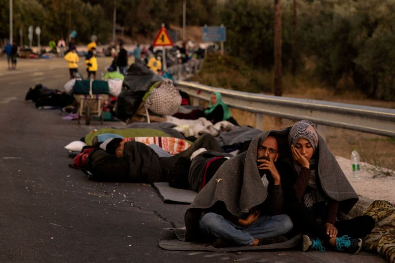 © Reuters. FILE PHOTO: Couple sits covered with a blanket as refugees and migrants camp on a road following a fire at the Moria camp on the island of Lesbos