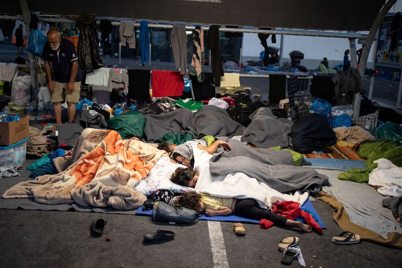 © Reuters. Refugees and migrants from the destroyed Moria camp sleep at the parking space of a supermarket, on the island of Lesbos