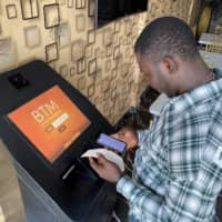 A man checks receipts after buying bitcoins with naira via a Bitcoin Teller Machine in Lagos. Monthly cryptocurrency transfers to and from Africa of under $10,000 (about ¥1.06 million) — typically made by individuals and small businesses — jumped more than 55 percent in a year to reach $316 million in June.  | REUTERS