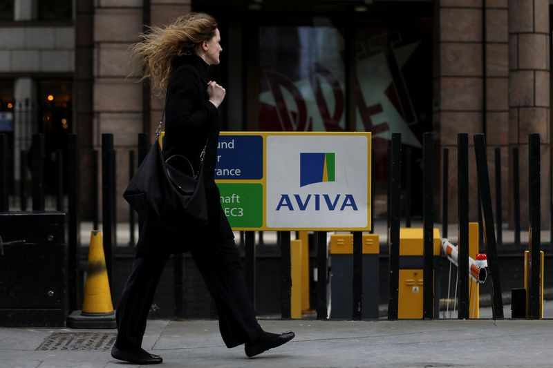 © Reuters. FILE PHOTO: A pedestrians walks past the Aviva logo outside the company head office in the city of London