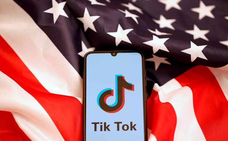 © Reuters. FILE PHOTO: TikTok's logo is displayed on the smartphone while standing on the U.S. flag in this illustration