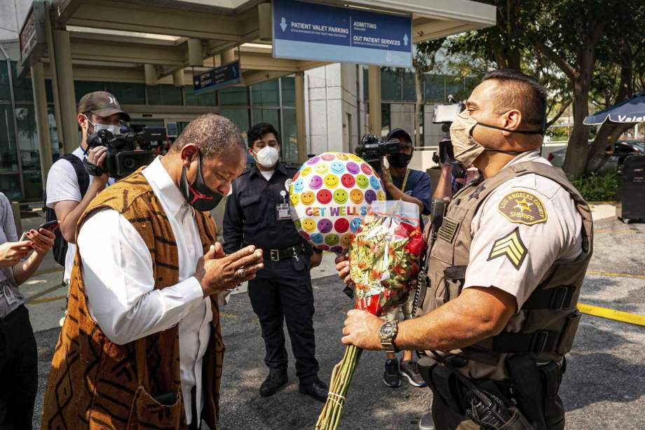 """Najee Ali, of Project Islamic Hope, presents Sgt. Larry Villareal, of the Los Angeles County Sheriff Dept., flowers for deputies recovering at St. Francis Medical Center in Lynwood, Calif., Monday, Sept. 14, 2020. The two deputies were shot Saturday while in their patrol vehicle in an ambush-style attack. Ali was especially troubled by reports that protesters were at the hospital chanting """"we hope they die"""" while the officers were fighting for their lives. (David Crane/The Orange County Register via AP) Photo: David Crane, AP / © 2020, Los Angeles Daily News/SCNG"""