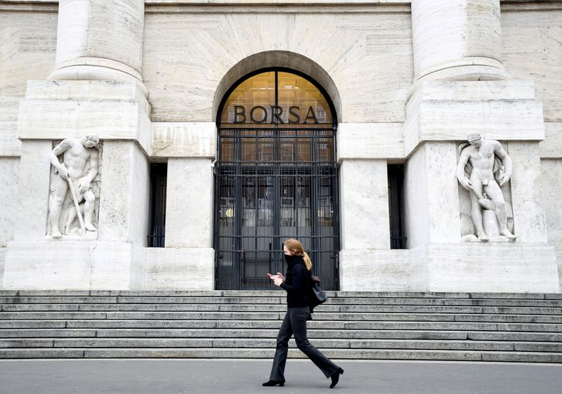 © Reuters. FILE PHOTO: A woman passes the Italian Stock Exchange in Milan