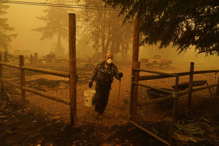 George Coble carries a bucket of water to put out a tree still smoldering on his property destroyed by a wildfire Saturday, Sept. 12, 2020, in Mill City, Ore. Photo: John Locher, AP / Copyright 2020 The Associated Press. All rights reserved.