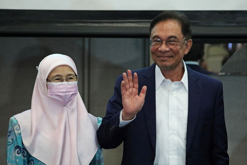 © Reuters. Malaysia opposition leader Anwar Ibrahim and his wife Wan Azizah Wan Ismail react after a news conference in Kuala Lumpur