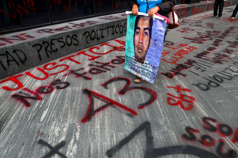 © Reuters. FILE PHOTO:  A relative of a missing student holds a poster with his image during a protest outside the Attorney General's office, in Mexico City