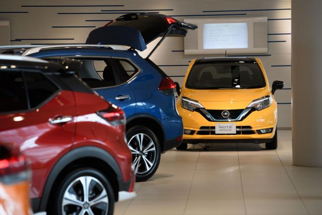 © Bloomberg. Nissan Motor Co. vehicles, including Note e-Power, right, stand on display in a showroom at the company's headquarters in Yokohama, Japan, on Tuesday, July 28, 2020. Nissan is struggling to restore profitability and sales after the November 2018 arrest of its former Chairman Carlos Ghosn and because a lack of new models left it ill-prepared to face a downturn in global vehicle demand amid the coronavirus pandemic. Photographer: Akio Kon/Bloomberg
