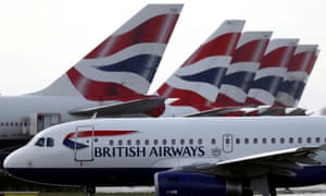 BA plane taxis past tail fins of parked aircraft