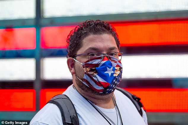 A new study found that 5.8% of nearly 300 coronavirus patients wore eyeglasses eight hours a day for nearsightedness compared to 31.5% of people in the Hubei province. Pictured: A man wears an American and Puerto Rico flag mask in New York City, September 2020