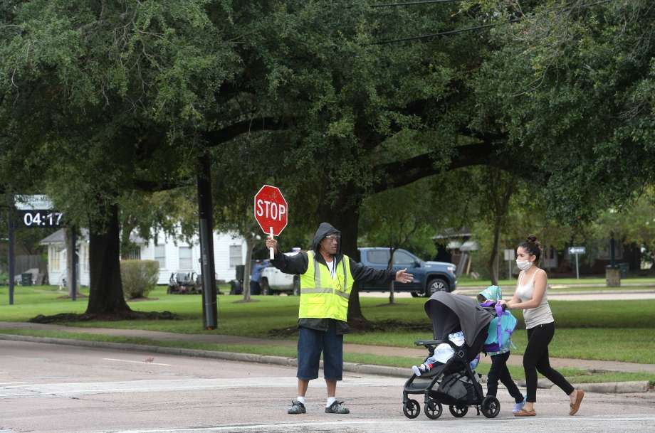 A crossing guard escorts a family as they make their way through Highland Avenue outside the newly expanded Pietzsch - MacArthur campus on the first day of BISD's second phase of reopening schools for in-person learning. Pre-kindergarten, kindergarten and 6th grades returned Monday. Photo taken Monday, September 28, 2020 Kim Brent/The Enterprise Photo: Kim Brent/The Enterprise