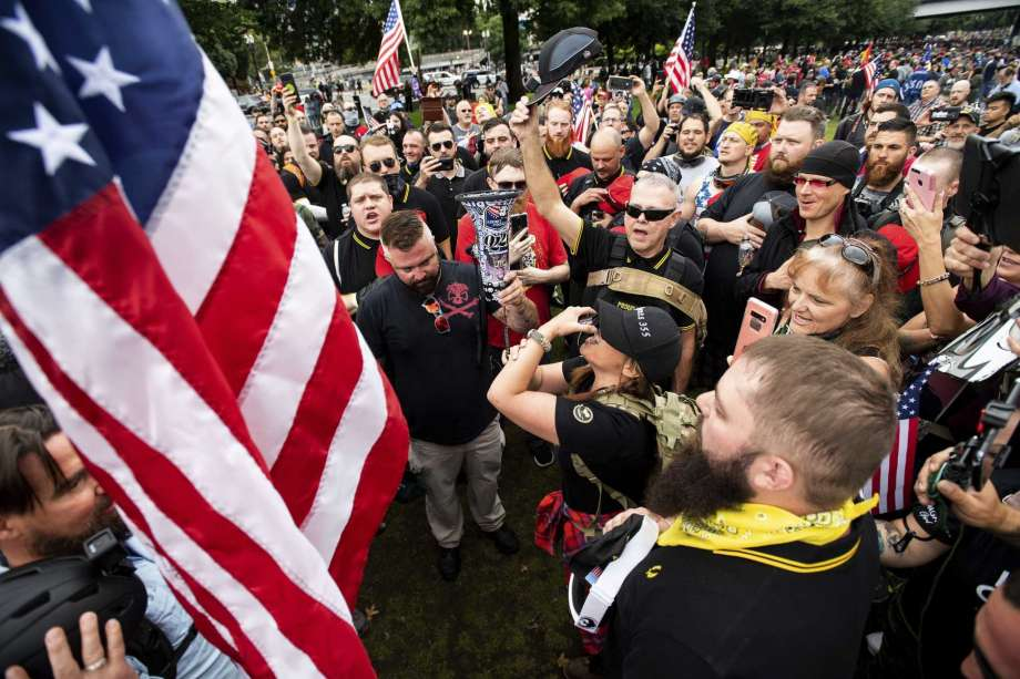 FILE - In this Aug. 17, 2019, file photo, members of the Proud Boys and other right-wing demonstrators plant a flag in Tom McCall Waterfront Park during a rally in Portland, Ore. At least several thousand people are expected in Portland on Saturday, Sept. 26, 2020, for a rally in support of President Donald Trump and his re-election campaign as tensions boil over nationwide following the decision not to charge officers in Louisville, Kentucky for killing Breonna Taylor. Photo: Noah Berger, AP / Noah Berger
